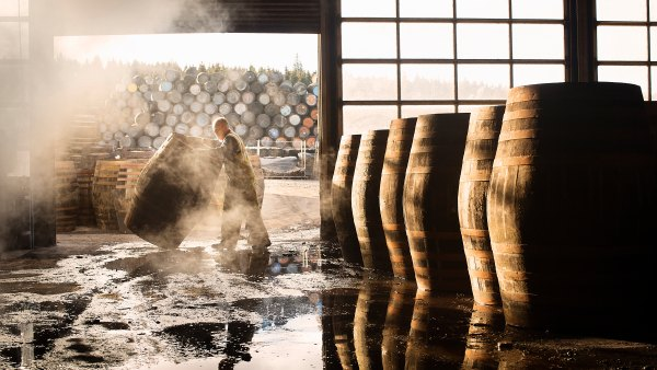 Man moving whiskey barrels