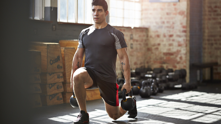 Man doing kettlebell lunges