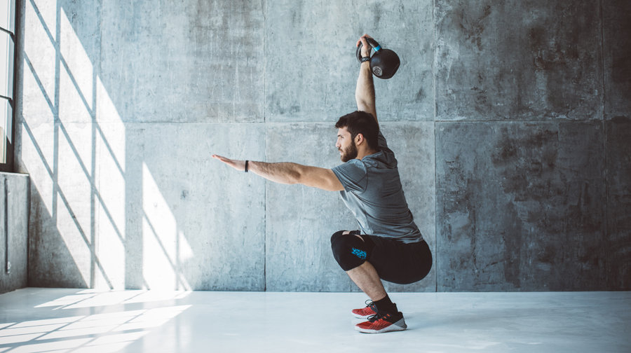 Male fitness athlete performing overhead squat with kettlebell