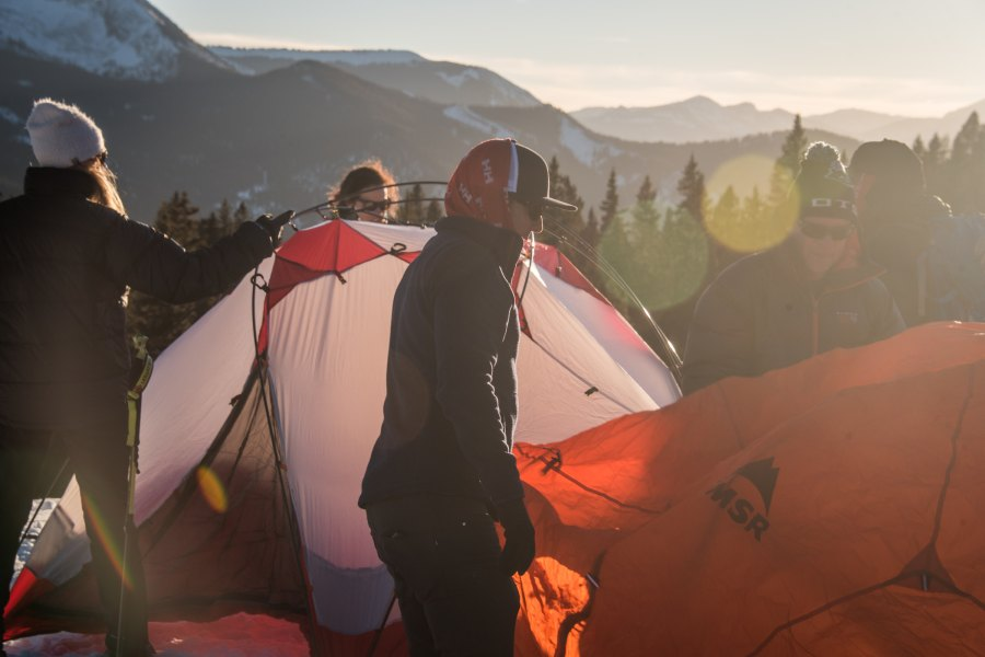 Campers setting up tents in winter