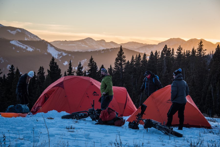 Men setting up camp in winter