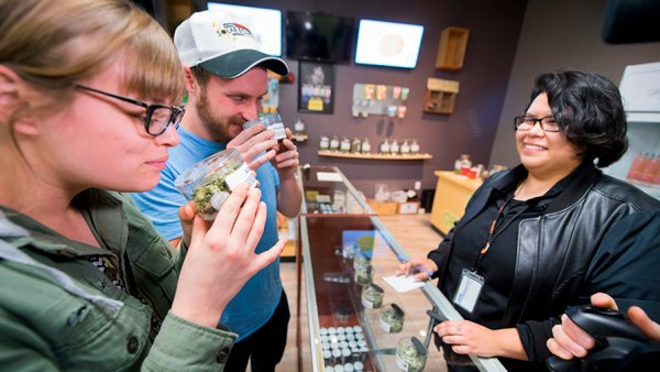 Tourists Laura Torgerson and Ryan Sheehan, visiting from Arizona, smell cannabis buds at the Green Pearl Organics dispensary on the first day of legal recreational marijuana sales in California, January 1, 2018 in Desert Hot Springs, California. / AFP PHOTO / Robyn Beck