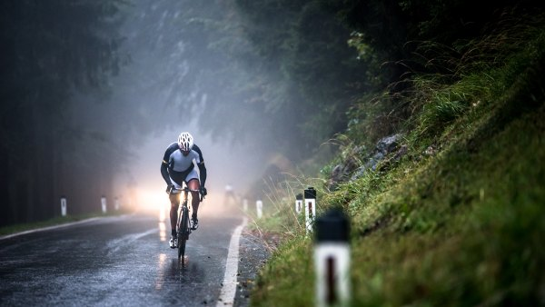 Man cycling on a wet road in rain,