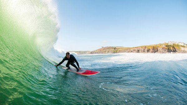 A surfer surfing his home break at Porthleven Beach. This location on the south coast offers perfect barrelling waves on the right conditions against a traditional Cornish coastal backdrop of cliffs and a fishing village.