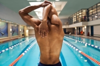Male swimmer stretching by pool indoors