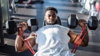 Man performing incline dumbbell chest press with resistance bands