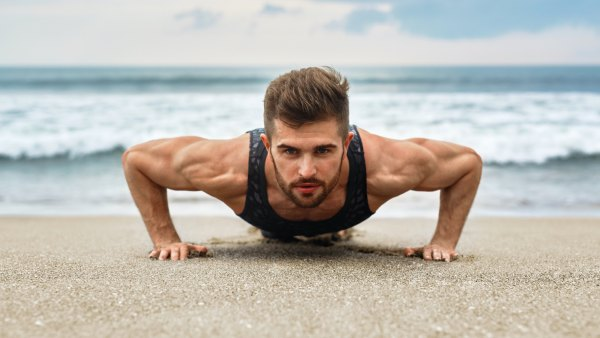 Man doing pushups on beach