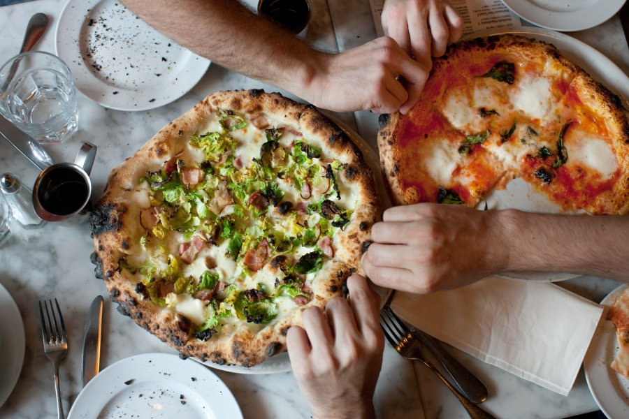 Hands dig in to two pizzas