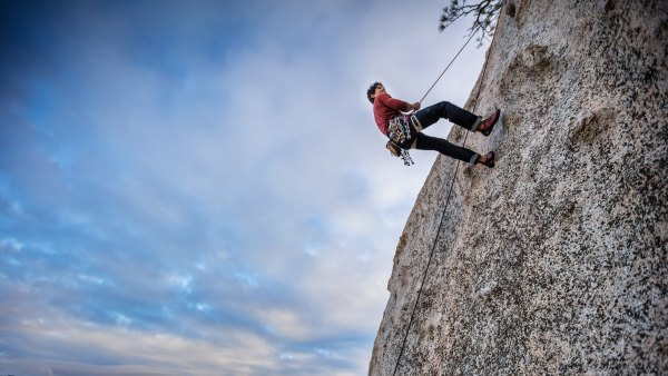 Rock Climber Rappelling Towards Camera