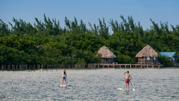 A woman stand up Paddling in Belize.