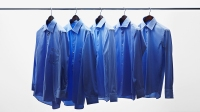Blue Dress Shirts Hanging On Clothes Bar Against White Background