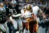 TAMPA, FL - JANUARY 22: Joe Theismann #7 of the Washington Redskins scrambles with the ball against the Los Angeles Raiders during Super Bowl XVIII on January 22, 1984 at Tampa Stadium in Tampa, Florida. The Raiders won the Super Bowl 38 - 9.