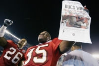 SAN DIEGO - JANUARY 26: Cornerback Dwight Smith #26 of the Tampa Bay Buccaneers celebrates as teammate Corey Ivy #35 holds a newspaper proclaiming that his team defeated the Oakland Raiders in Super Bowl XXXVII at Qualcomm Stadium on January 26, 2003 in San Diego, California. The Buccaneers won 48-21.
