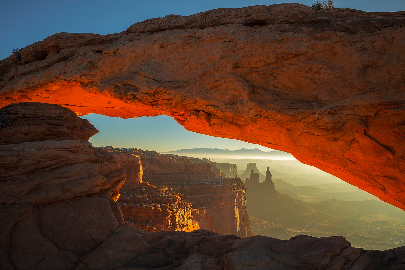 A winter sunrise illuminates the underside of Mesa Arch in Canyonlands National Parks, Utah.