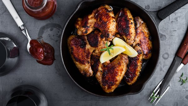 Smoky roast chicken wings in cast iron pan on blue dark background viewed from above