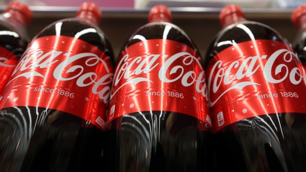 Bottles of regular Coca Cola soft drink, manufactured by Coca-Cola Co., stand on display at the Tesco Basildon Pitsea Extra supermarket, operated by Tesco Plc, in Basildon, U.K., on Tuesday, Dec. 1, 2015. Many European food retailers are coming to terms with persistently low inflation as well as consumers who remain frugal yet purchase food more frequently.