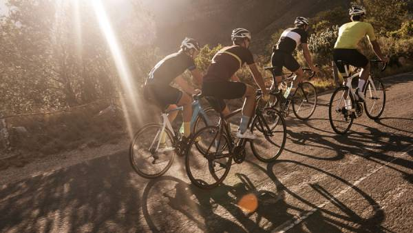 Group of male cyclists climbing hill