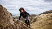 Young male hiker stepping from rock