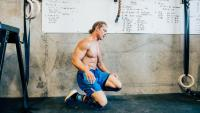 Fit man resting in CrossFit gym
