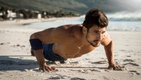 photo of a fit man doing push ups on the beach