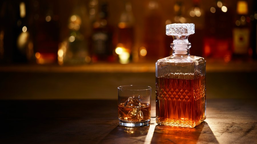 A Bourbon Whiskey Decanter and Bourbon on the Rocks in a Tumbler sitting on a bar with bottles in the background.