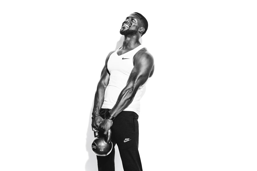Kevin Hart posing with kettlebell on set of photoshoot