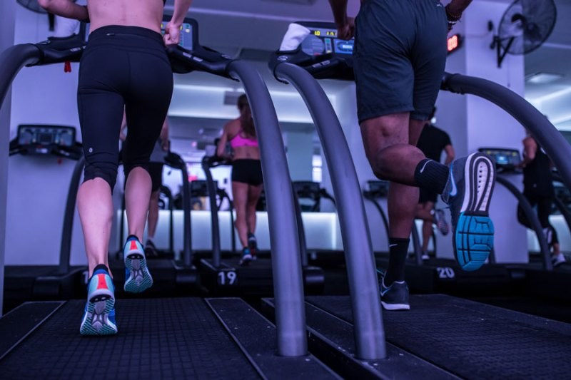 Man and woman running treadmill at Mile High Run Club class