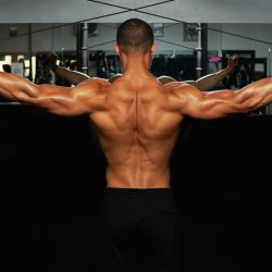 Muscular man using cable machine