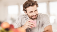 Young man drinking smoothie at kitchen counter