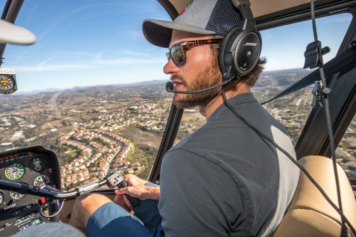 Scott Easwood in the pilot's seat of a Robinson R44 helicopter.