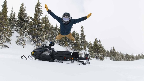 A man wearing a helmet belly flops into the snow from his snowmobile.