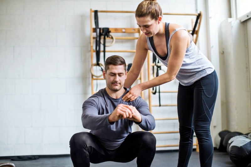 Female personal trainer assisting man doing exercising at gym