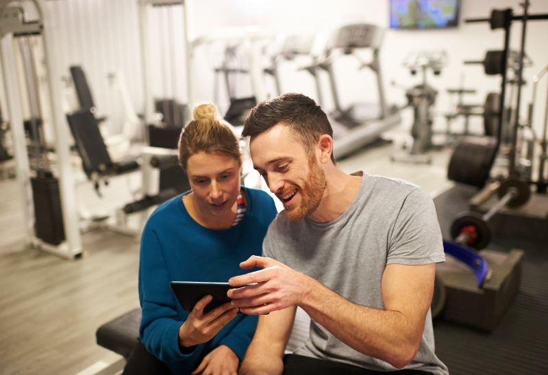 A woman and personal trainer sit on a weight bench and look at a digital tablet together.