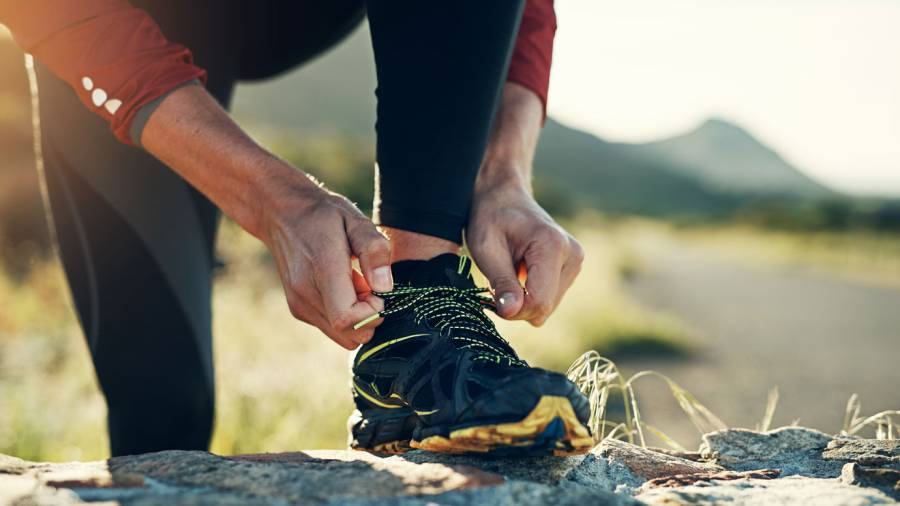 Trail runner tying shoes