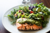 Salmon fillet topped with arugula pesto and salad