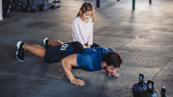 Father doing pushups with daughter sitting on his back