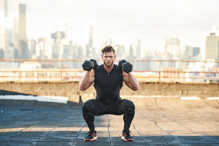 Man doing dumbbell squat on rooftop