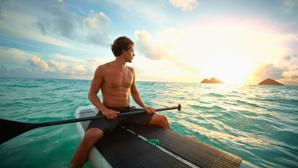 Muscular man on paddle board in tropics