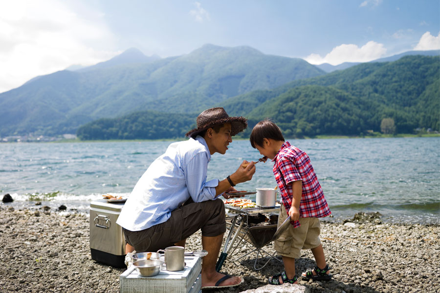 Father and child eating a barbecue by the lake