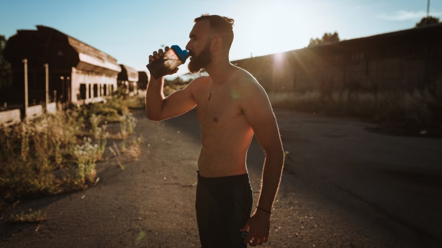 Shirtless athlete drinking water after a hard exercise outdoors