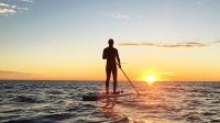 Spanish man practicing paddle surfing when sunrise at Barcelona beach