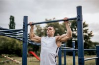 Man doing pull ups in the local park