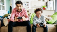 A father and son are concentrating while sitting down at home playing video games together.