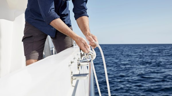 Man on motor yacht tying a knot