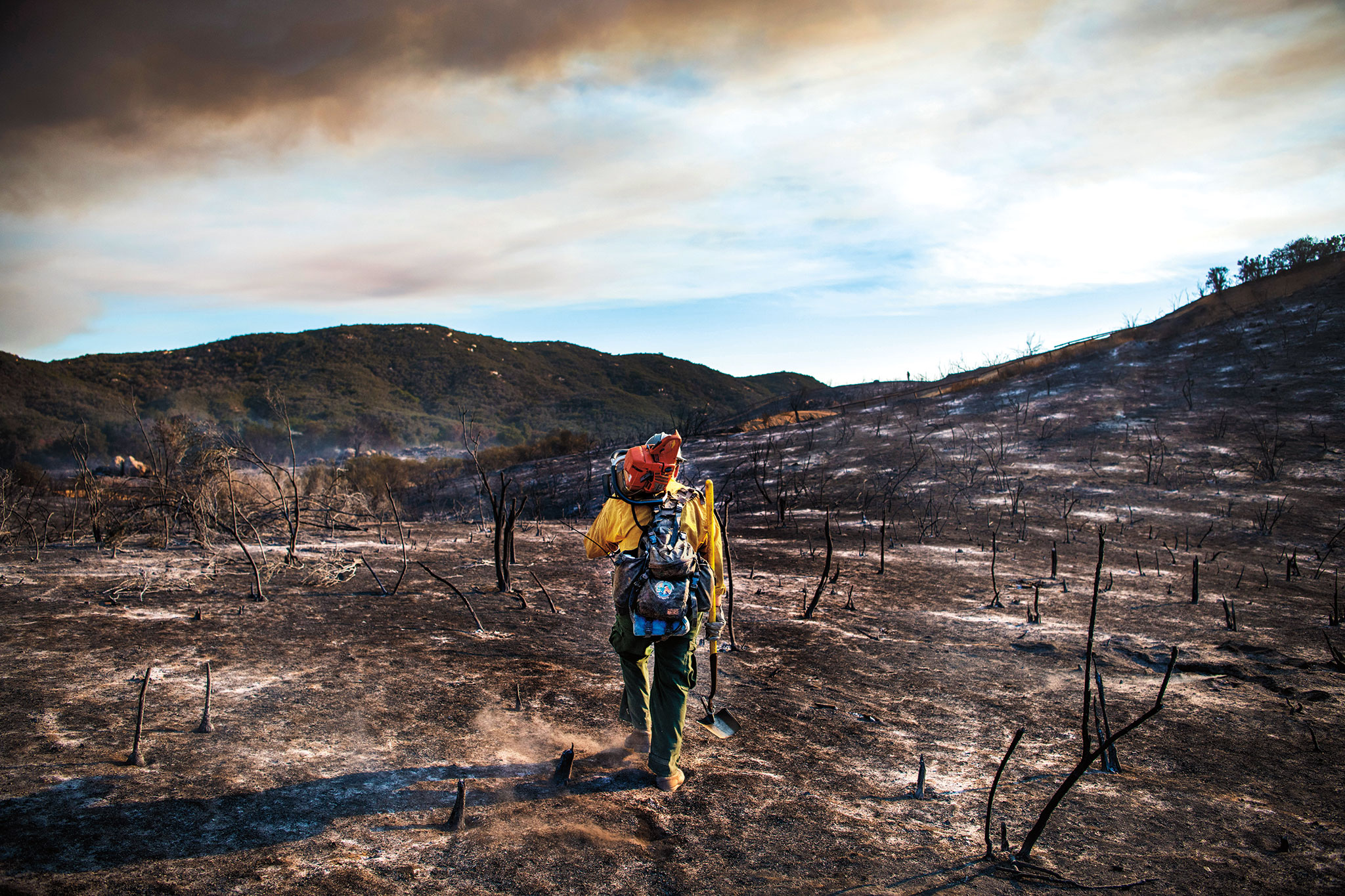 A hotshot carries a chainsaw to his crew, cutting a firebreak during California's 2017 Wildomar Fire, which burned 866 acres