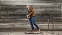 Smiling man with coffee to go on skateboard in front of wooden wall