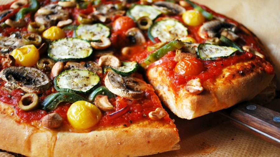 Vegetarian pizza on whole wheat crust with bell pepper, zucchini, mushrooms, and olives