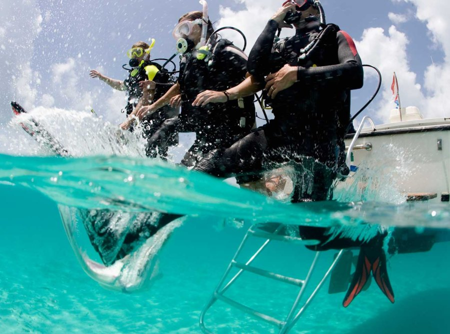 Scuba divers entering water from boat, Key Largo, Florida.
