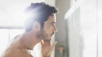 Man checking beard in bathroom mirror