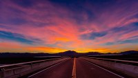 Highway overpass above Interstate 15, south of Las Vegas, Nevada at sunset with yellow line. (Photo by: Visions of America/UIG via Getty Images)